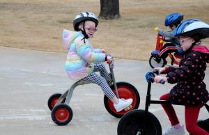 Students  ride tricycles outside