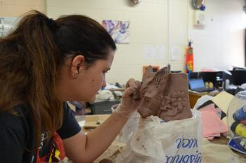 Paige working on a clay totem pole fox.