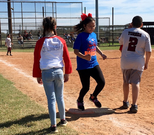 First base judge Jolie Lankford watches Eryiann Deleon safely  touch the base.