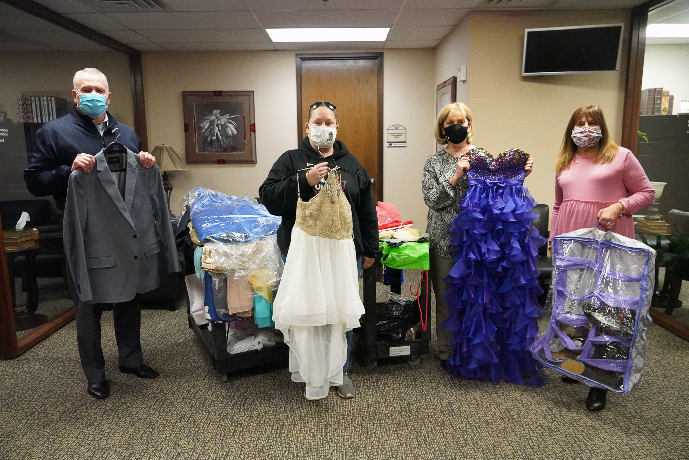 About 500 dresses and suits have been donated for the upcoming Prom Dress/Suits Boutique planned for next month by the Union PTA Council. PTA organizer Jean Jones is collecting all the donated garments so they can be dry-cleaned before the boutique. Jones is pictured here with the white dress, along with Superintendent Dr. Kirt Hartzler, and executive administrative assistants Jamie Ward and Karen Howard at the Education Service Center. The boutique will take place March 11, March 13 and March 22- 24 in the Redzone Room at the UMAC.  Students will be able to select and take home garments at no charge for the prom. Because of the pandemic, changes have been made to the prom in an effort to promote safety of the students. This year, prom will be for seniors and their dates only at the Expo Center from 8 p.m. until midnight on Saturday, April 24. For more information about the boutique, contact Jones at Jeanmjones12@yahoo.com or 918-978-5999.