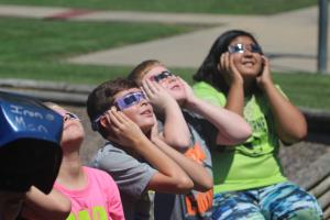 Children watch the eclipse with the help of high school students.