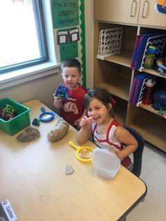 Scientist examining rocks & shells in the green center.