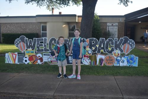 Welcome back sign with students