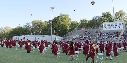 Seniors tossing caps from HC newspaper