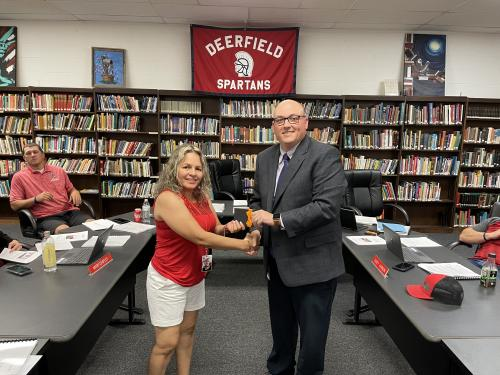 Mr. Eslinger presenting Carmen Llamas with the Spartan Pride award, in the high school library