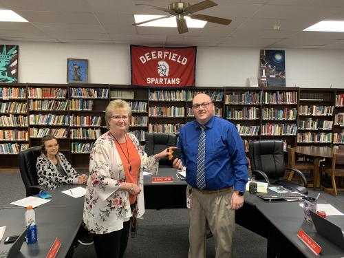 Mr. Eslinger presenting Mrs. Tackett with the Spartan Pride award, in the high school library