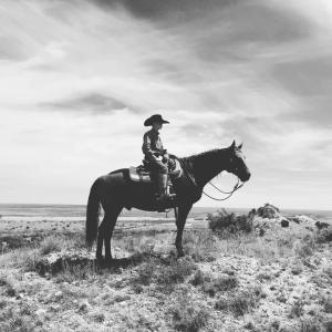 Payton Nelson riding his horse up the caprock.