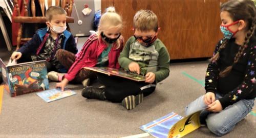 Preschool students reading library books.