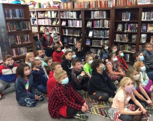 students listen as book is read in library
