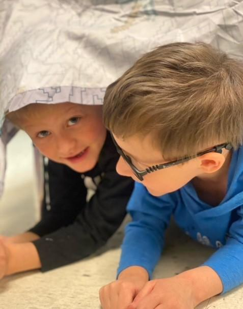 Preschool students playing in play fort