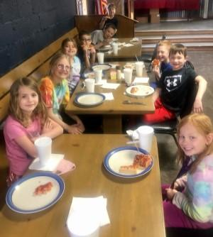 Elementary students eating pizza