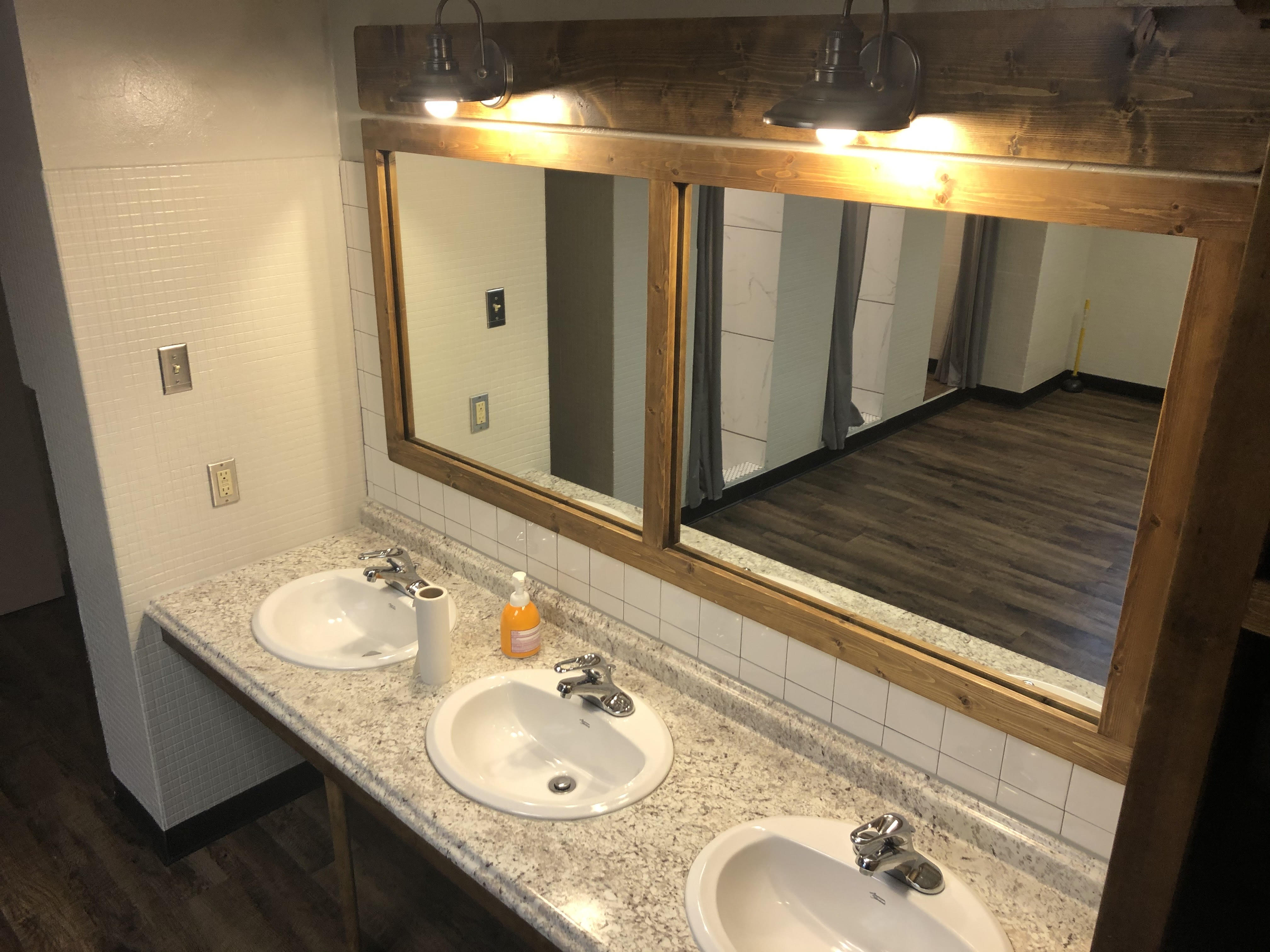 Long mirror with wood trim, two lights and three sinks
