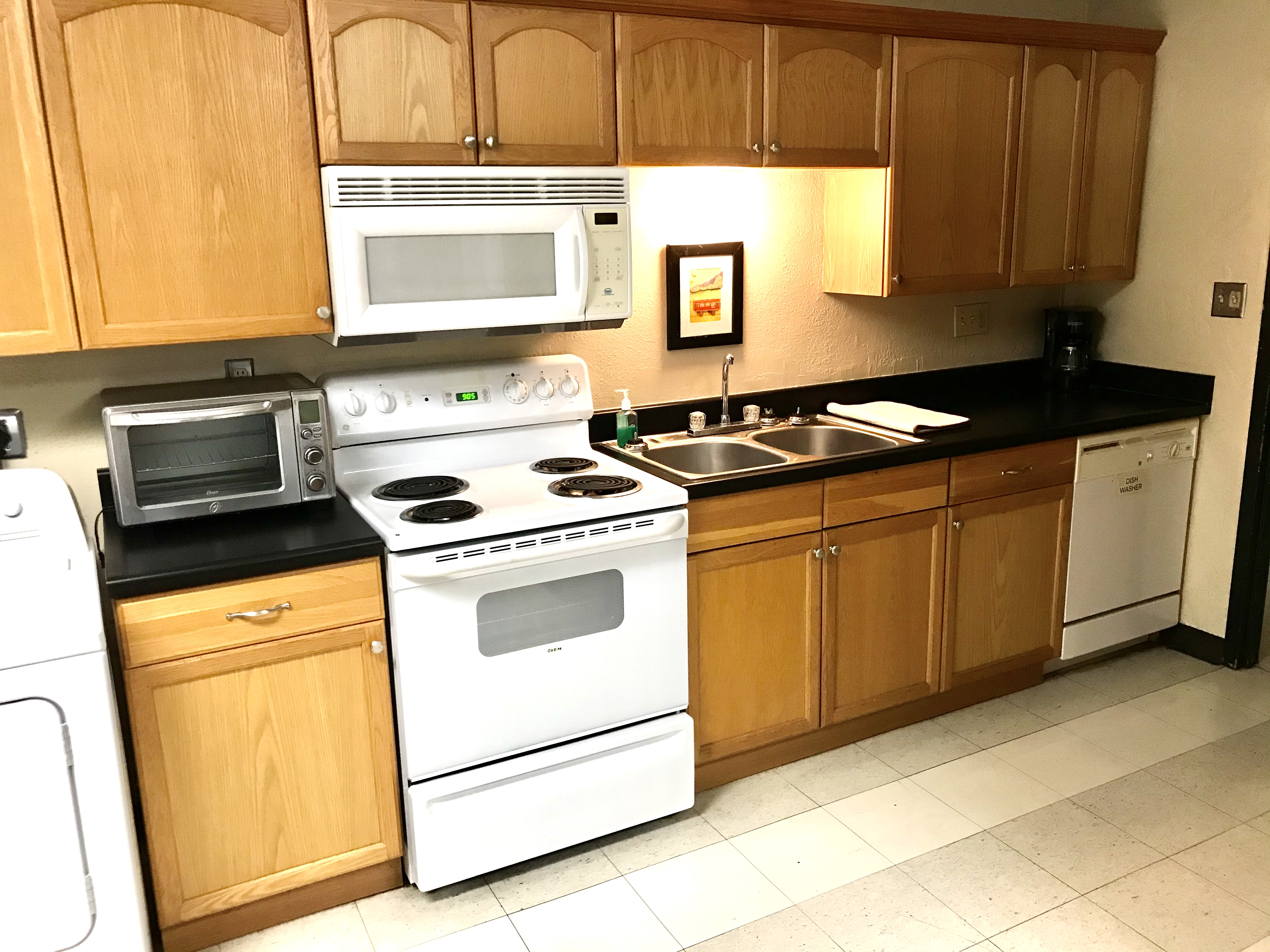 Counter, cabinets shown with a stove, sink and dishwasher