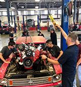 Students working on a car engine