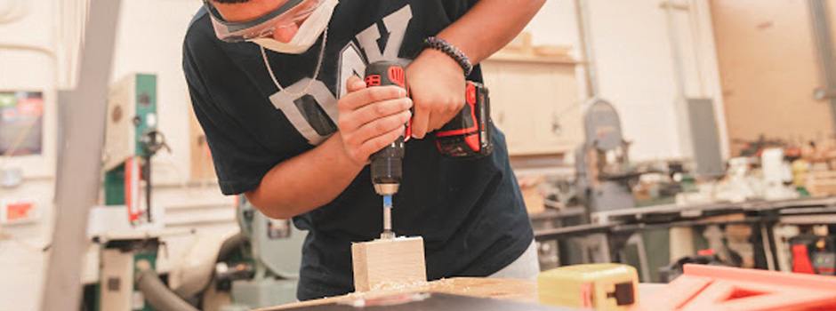 Student drilling into a piece of wood.