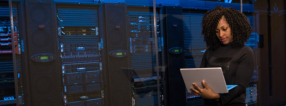 Network systems analyst holding a laptop, standing in front of network servers