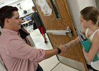 Mr. Lamarche shaking hands with a student