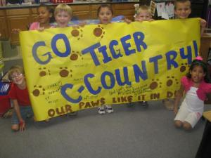 FIRST GRADERS LOVE TO SHOW THEIR CROSS COUNTRY PRIDE AND SUPPORT.