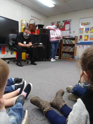 Chad Wilson and Laura Thomas reading their book Marty's Magic Rabbit to the classroom