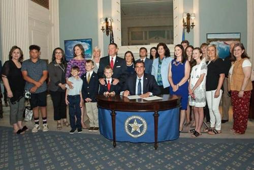 Decoding Dyslexia Oklahoma members stand with Governor Kevin Stitt as he signs HB 1228.  HB 1228 requires all Oklahoma teachers to have training in dyslexia education annually, starting with the 2020-2021 school year.