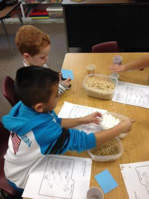 Gael and Trenton follow a recipe to make squirrel feed in their math lab.