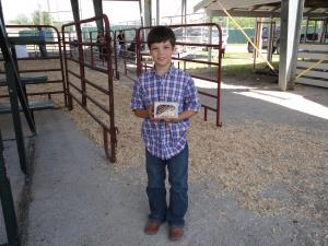 Bryce showing his belt buckle he won for showmanship