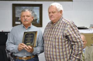 Rick George presents A.J. Ferguson with a plaque.