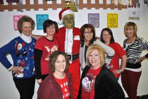 Elementary teachers pose with the Grinch