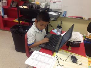 First grade student in Mrs. Barrios' class researching for his PBL.