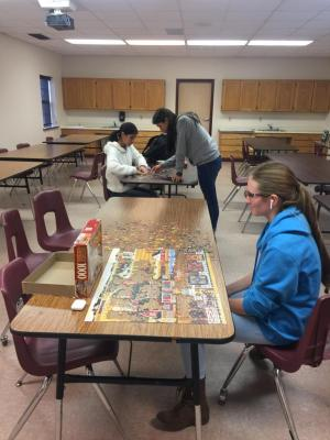Students working on a puzzle after a long week of finals