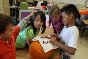 Group 1 tracing their design onto the pumpkin.