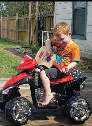 My youngest playing his guitar