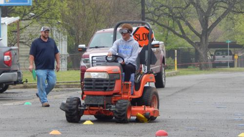 student driving the tractor through the course