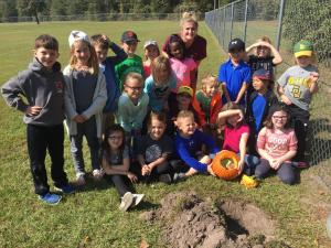 Class picture before we bury the pumpkin filled with trash!
