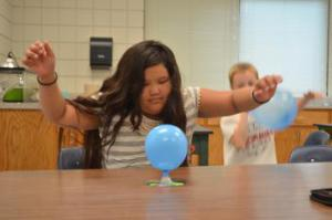 Sunshine experiments with different sizes of balloons to see the effects of air presure.