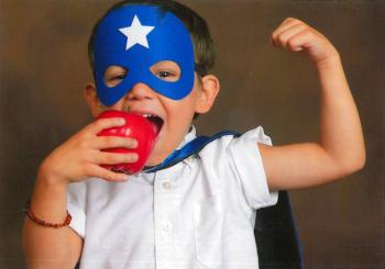 Super hero kid eating an apple