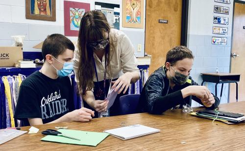 Mrs. Lemp helps students with an art project.