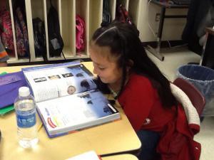 Karina is using her reading skills.