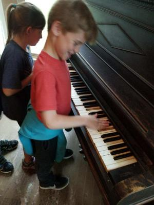 Playing an old piano at Harn Homestead