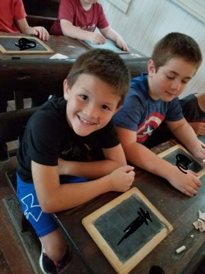 Writing their names in the old school house - Harn Homestead