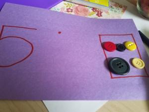 Students put buttons down according to the number on the paper mat.