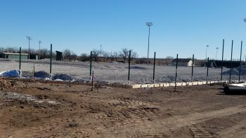 At Andover High School, crews are grading the base rock and installing concrete curbs near the ball fields where the new turf will be installe