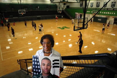 Effie Milam, mother of Ron and former MHS English Teacher, stands in Major Ron D. Milam Memorial Gymnasium on the MHS campus.