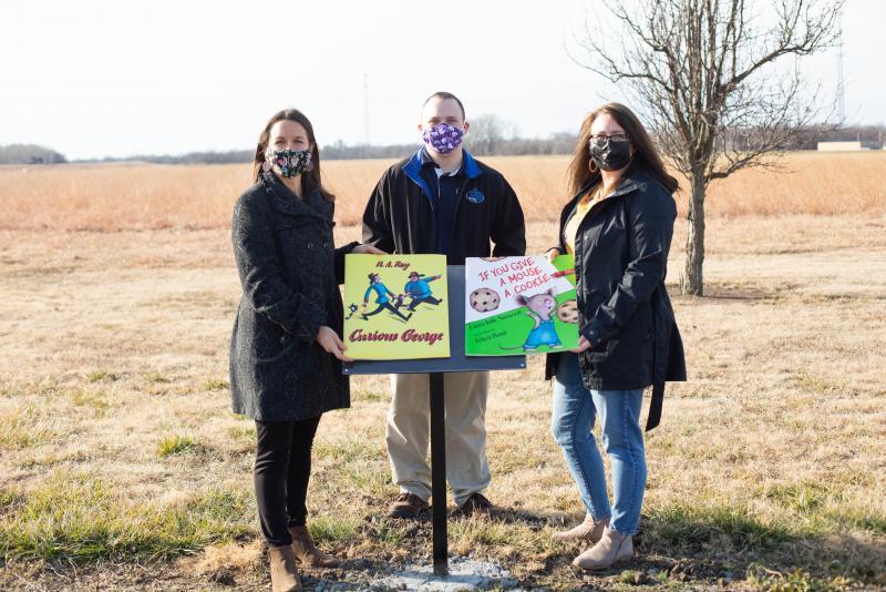 Community Partners work to install StoryWalk at Poplar Walking Trail