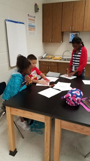 Students teach each other how to plot the epicenters of earthquakes.