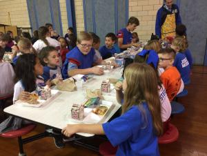 Football players eating lunch with students