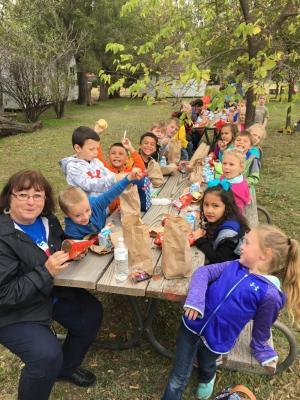 Kindergarten students taking a lunch break on their field trip.