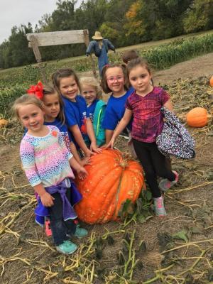 Kindergarten girls posing with a GIANT pumpkin.