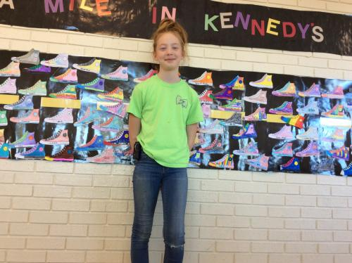 Kennedy in front of banner