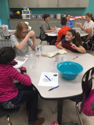 Students measure water to determine the amounts of saltwater and freshwater we have on Earth.